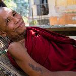 Starý mnich v klášterní zahradě v Mandalayi