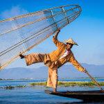 Pózující rybář na jezeře Inle s typickou kůželovitou sítí