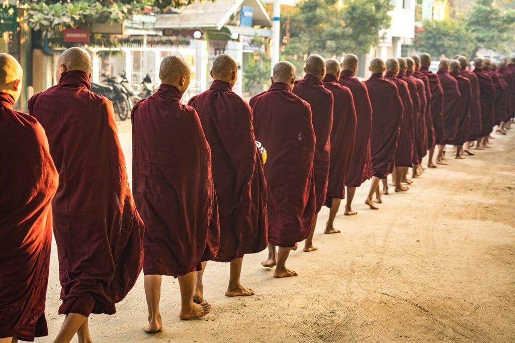 Mnichové při východu slunce přijímající almužnu