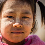 Mladá dívka s thanakou na tváři, kterou Barmánci používají jako orchranu před sluncem