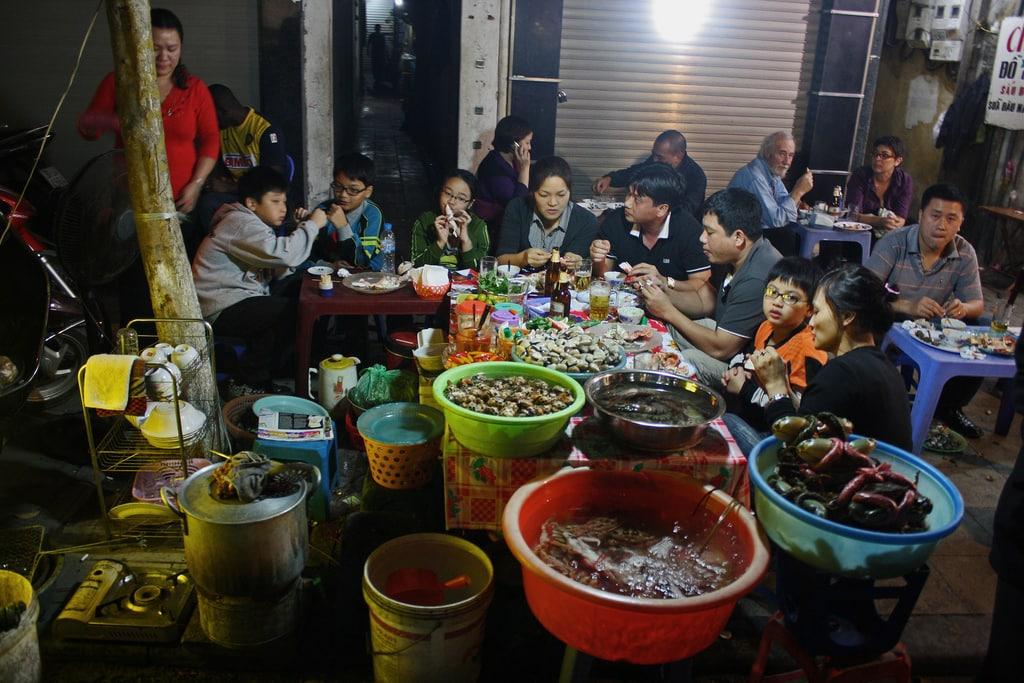 Vietnamská rodinka večeřící v pouliční restauraci v Hanoji