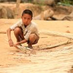 Místní chlapec plete rohože