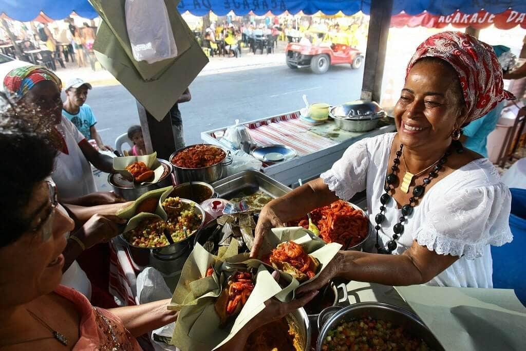 Tradiční pochoutka acarajé servírovaná s typickým úsměvem
