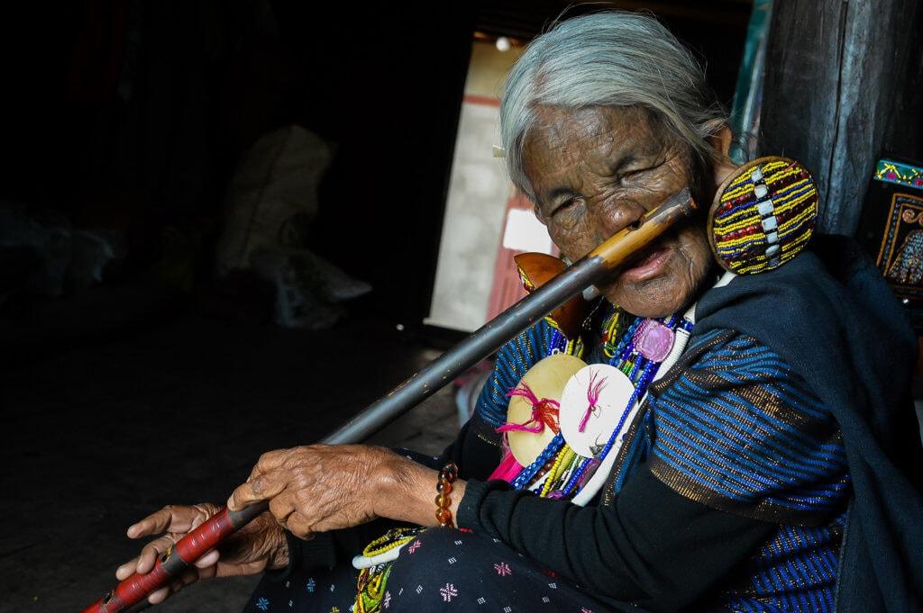 Potetovaná babička ve státě Chin hraje na nosní flétnu (foto: Julia Polok)