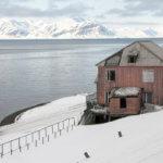 Polorozbořené budovy v přístavu v Barentsburgu