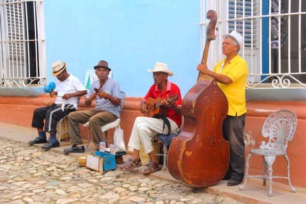 Pouliční umělci v uličkách starého karibského městečka Trinidad
