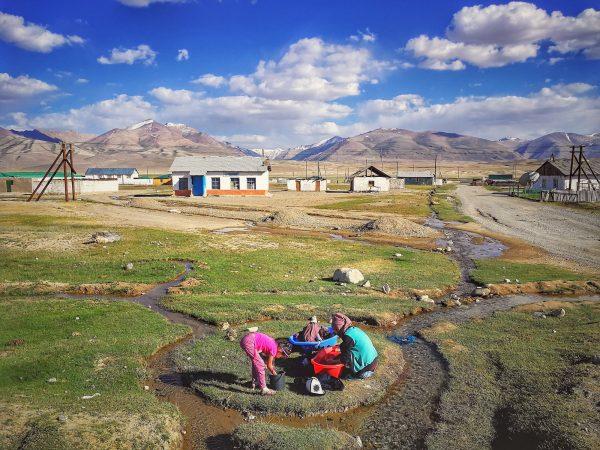 Ženy z kyrgyzské menšiny perou prádlo v potoce